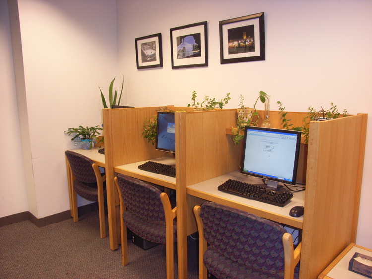 Three wooden cubicles with computers