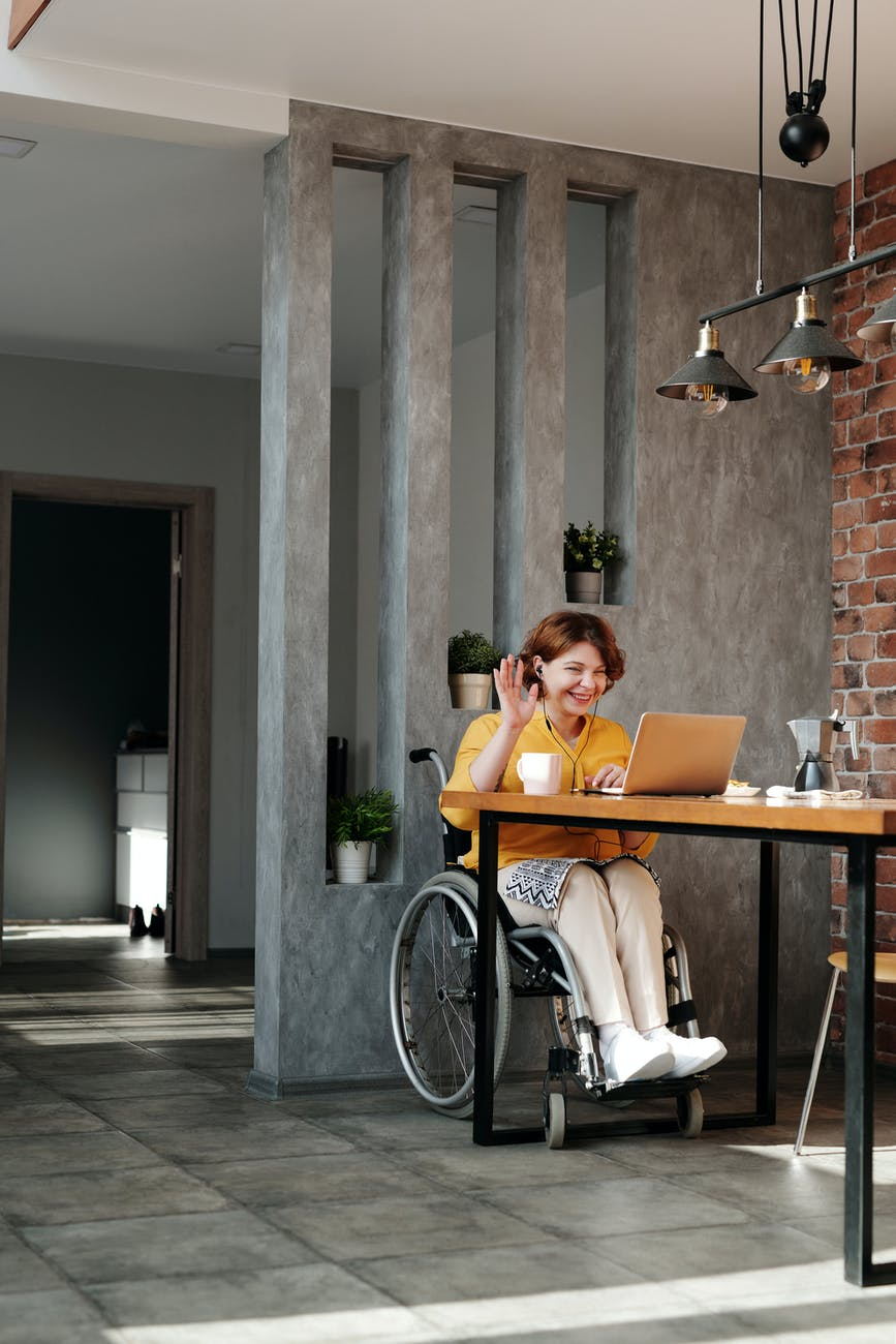 woman in wheelchair greeting someone on an online call